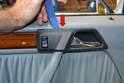 Use the trim removal tool and gently pry the switch and handle trim piece away from the door panel (red arrow).