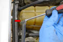 Use a flathead screwdriver and remove the hose and clamp for the radiator to reservoir overflow hose (red arrow).