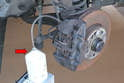 You are going to go into the vehicle and pump the brake pedal, so make sure the catch bottle cannot spill (red arrow).