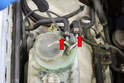 Windshield Fluid Heater- Begin by using a flathead screwdriver and removing the two clamps and coolant hoses from the top of the unit (red arrows).