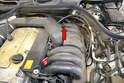 The sensor is located in the air intake tube on the left side of the engine just above the intake manifold (red arrow).