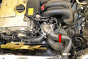 Locate the power steering reservoir just below the thermostat (red arrow).