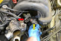Separate the wiring harness for the throttle body by pivoting back the clip (red arrow) and pulling the plug from the mount (yellow arrow).