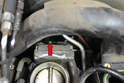 Remove the small throttle return spring from the rear of the throttle body (red arrow).