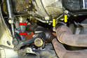 Using a 13mm socket with a series of extensions, remove the two bolts holding the exhaust pipes to the front manifold (red arrows) and rear manifold (yellow arrows).