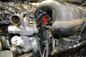 Reach in between the manifold and water pump and remove the two vacuum hoses attached to the lower section of the manifold between the number two and three intake runners (red arrow).