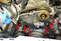 Remove the six 13mm bolts holding the timing chain cover to the front of the head (red arrows).