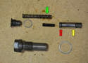 Next install the thrust pin (yellow arrow) and detent spring or clip (red arrow) into the tensioner housing.