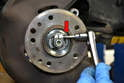 Use a 5mm Allen key (red arrow) to loosen the clamp on the axle nut.