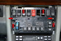 With the trim piece removed use a Philips head screwdriver and remove the six screws holding the climate control unit to the center console and upper switch plate (red arrows).