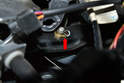 Use a screwdriver and remove the pin clip from the pin and slip the pin out from the brake pedal (red arrow).