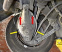 With the car safely supported remove the lower control arm cover by unscrewing the two 10mm screws on the cover (red arrows) and unclipping the cover from the arm (yellow arrows).