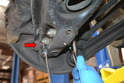 Remove the 13mm nut from the drop link (red arrow), slightly raise the control arm and remove the bolt.