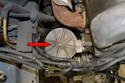 Locate the oil filter towards the lower front right of the engine and remove with your oil filter housing lid with a 13mm socket (red arrow).
