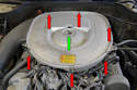 Undo the six clips (red arrows) holding the air housing lid on as well as the wing nut (green arrow) in the center of the air cleaner housing.