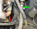 This photo illustrates where the ground strap connects to the back of the power steering bracket (red arrow) on the engine side and to the coil mount (green arrow) on the chassis side.