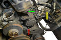 With the power steering pump moved (yellow arrow) to the side you can see the TDC harness (green arrow) running down between the oil pump and A/C bracket to the sensor (red arrow).