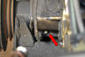 It is secured to its mount on the front of the engine just off to the side of the vibration dampener by an 8mm bolt (red arrow).