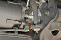 The red arrow shows the crankshaft bearing bolt on the left side of the engine.