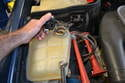 Once the car is cold, begin by removing the cap on the coolant reservoir to release any residual pressure.