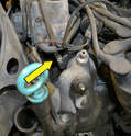 Remove the clamp from the large hose coming out of the thermostat housing (yellow arrow).