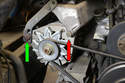Loosen the 17mm bolt (red arrow) attaching the alternator to the solid mount.