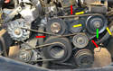 This photo shows the route of the two power steering pump and cooling pump belts (red arrows), the location of the power steering pump pulley (green arrow) and the three 13mm nuts and bolts connecting it to the car (yellow arrows, one is hidden).