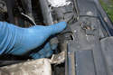 Working at the upper radiator on the right side lift up on the clip that holds the radiator to the radiator support.