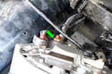 Remove the 13mm fastener (green arrow) that mounts the alternator output wire to the battery cable.