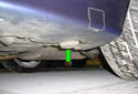 This photo illustrates the left side rear pad (green arrow) at the rear of the rocker panel in front of the driver side rear tire.