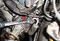 Use a 17 mm wrench or line wrench and loosen the power steering pressure feed hose.