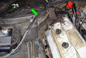 Working at the back of the valve cover, lift up the black sheathing (green arrow) that runs vacuum lines to the right side inner fender.