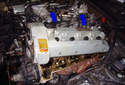 Slide the valve cover upward in the direction of the blue arrows to move it out of the engine compartment.