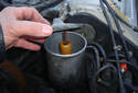 Remove the power steering fluid reservoir cover by pulling up on it.