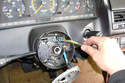 Feed the wiring harness through the opening in the steering column and pull the connector out of the steering column.