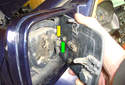 Pivot the outside of the mirror to the right until the ball socket on the glass (green arrow) pops off of the ball joint (yellow arrow) on the mirror assembly.