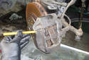 Front Brake Pads Use a roll-pin punch and a hammer to tap out the upper brake pad retaining pin.