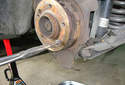 Pull the spring out of the lower brake pad shoe.