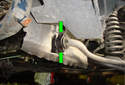 Follow the sway bar to the chassis mounting bracket and remove the two 13mm fasteners (green arrows).