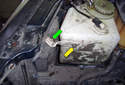 This picture illustrates the washer fluid reservoir behind the right side headlight on the right side inner fender.