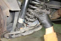 Remove the brake pad wear sensor harness from the lower control arm mount.