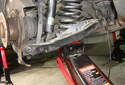 With the hydraulic jack supporting the lower control arm, remove the four fasteners you just loosened.