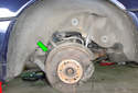 This picture illustrates the left side rear wheel well with the rear wheel off of the car.