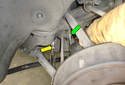 Using a wrench remove the 17mm fastener (green arrow).