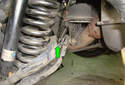 Remove the brake pad wear sensor harness from the second lower control arm mount (green arrow).