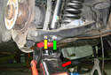 Place a jack under the lower control arm (red arrow).