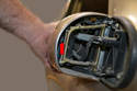 While holding the housing folded inward you will need to insert a flat head screw driver between the inside of the housing and the small clip that holds it in place (red arrow).