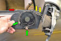 This photo illustrates the metal wire (red arrow) and two metal prongs (green arrows) that hold the mirror to the assembly.