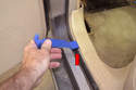 Remove the lower trim panel along the rear floor using your trim tool (red arrow).
