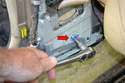 Remove the large T45 bolt holding the seat belt retraction unit to the lower mount (red arrow).